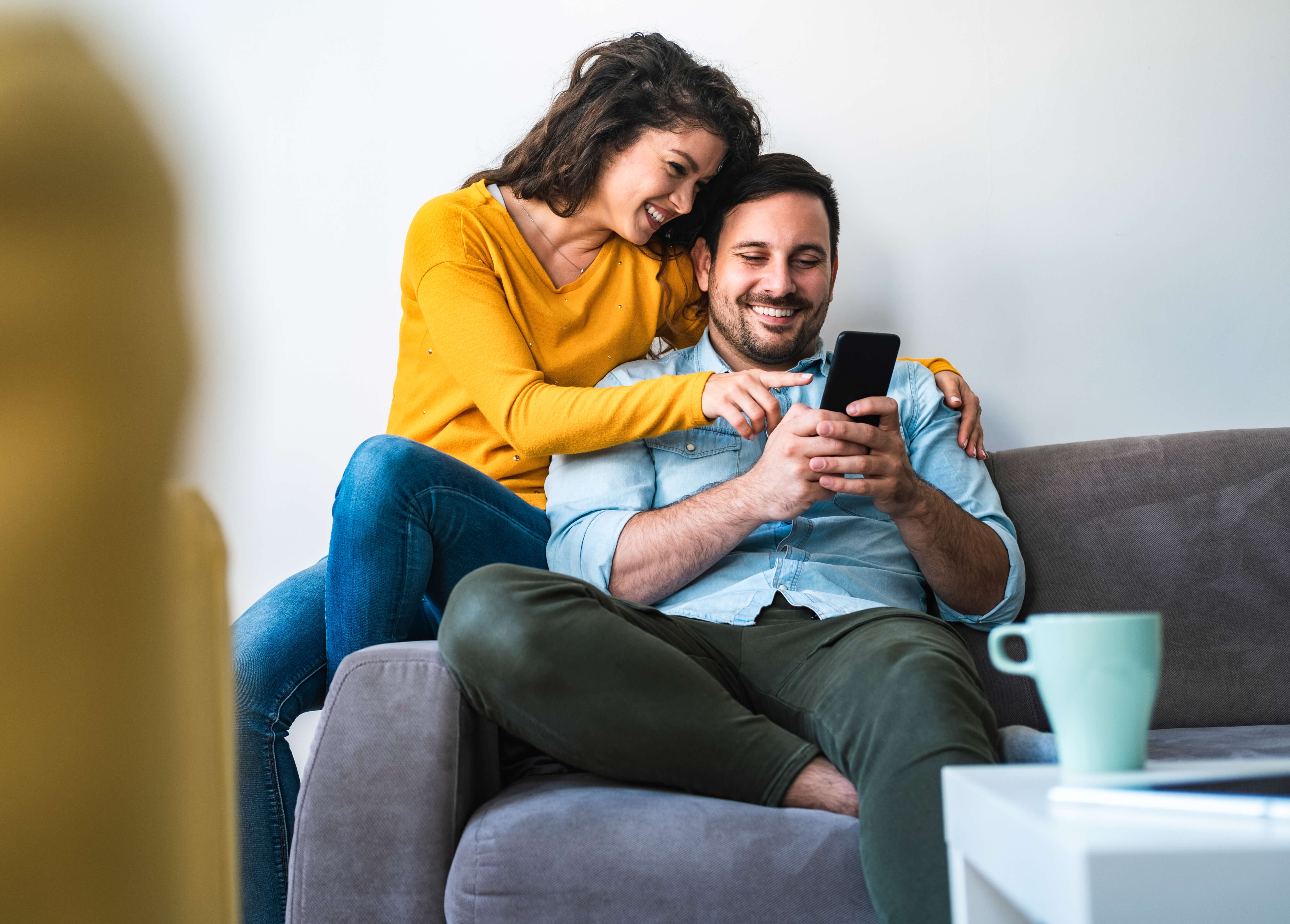 Couple hugging and sitting on the couch while looking at a phone