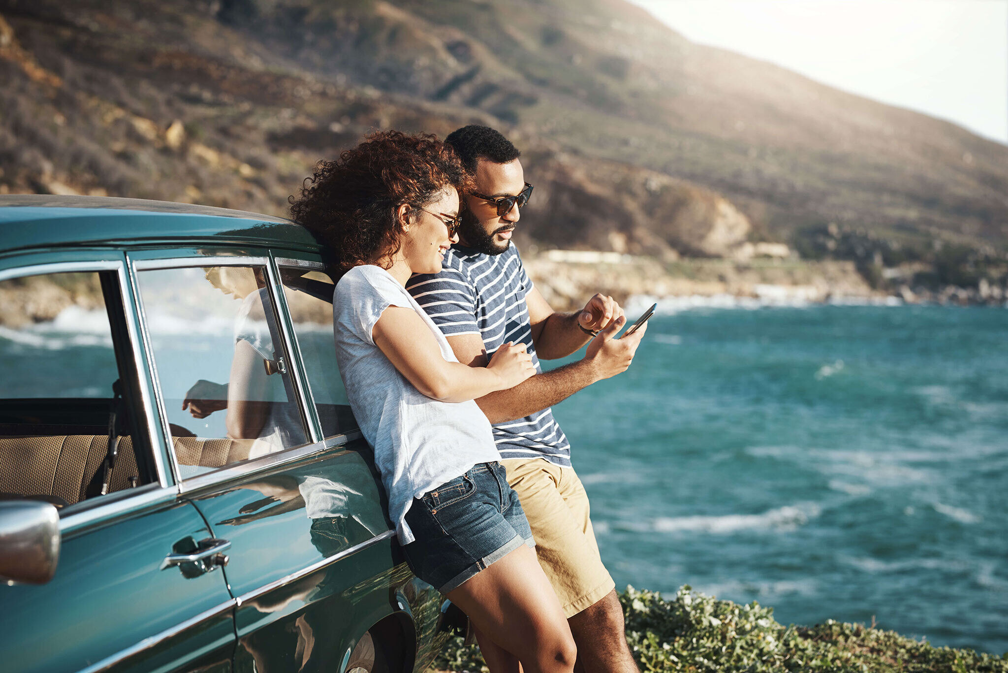 Couple on a road trip standing by the ocean