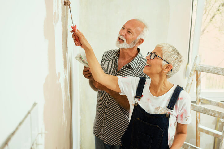 Couple painting a living room
