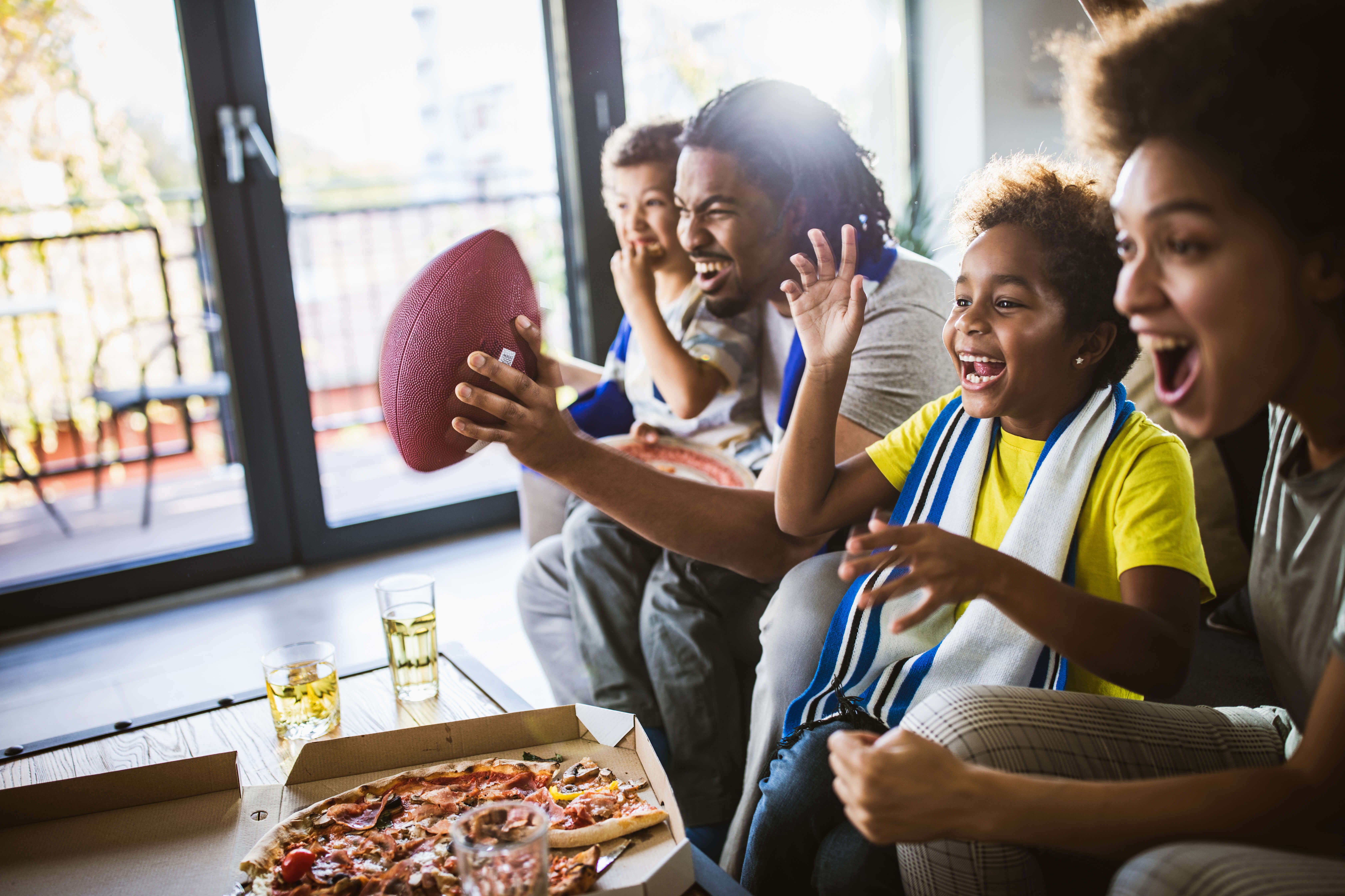 Family eating pizza and watching football together
