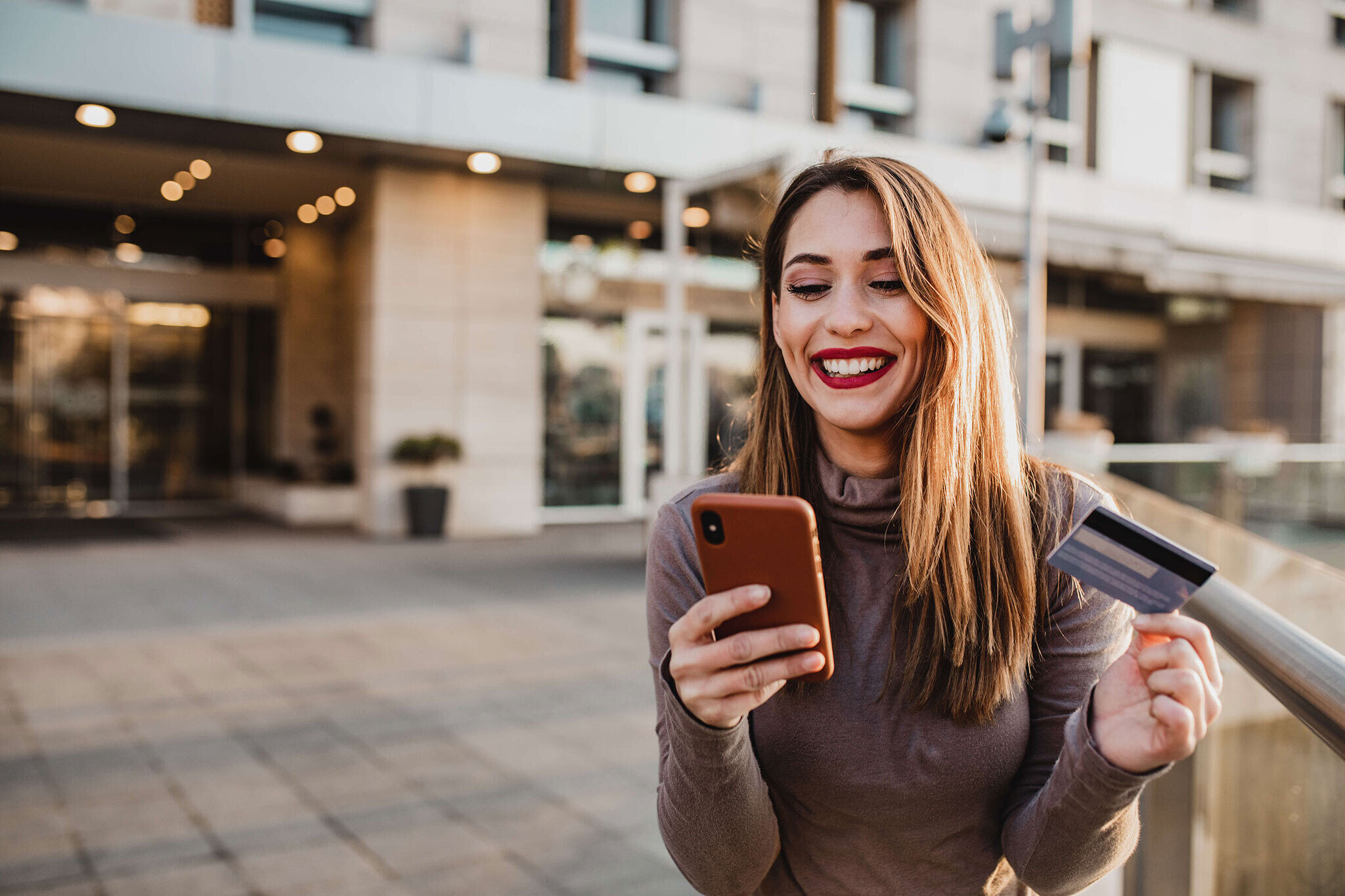 Gen z woman holding credit card and phone