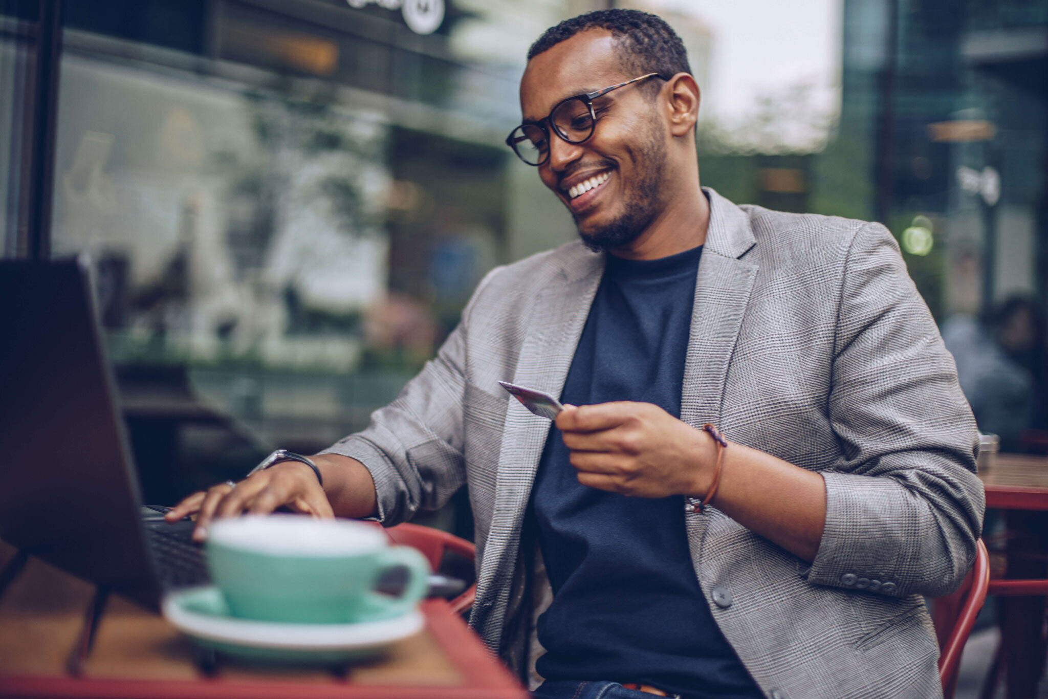Man smiling and sitting at a cafe with his credit card and computer