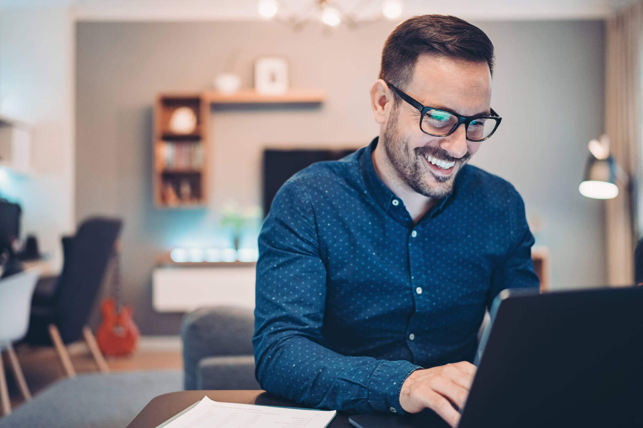 Man wearing glasses and smiling while working on computer