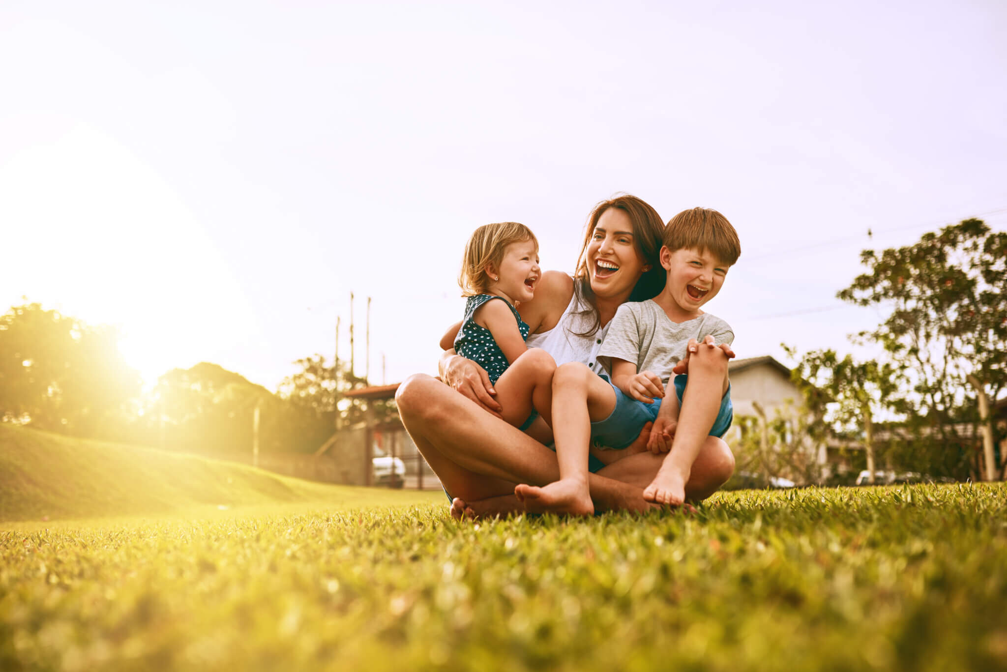 Mom and two young children laughing together