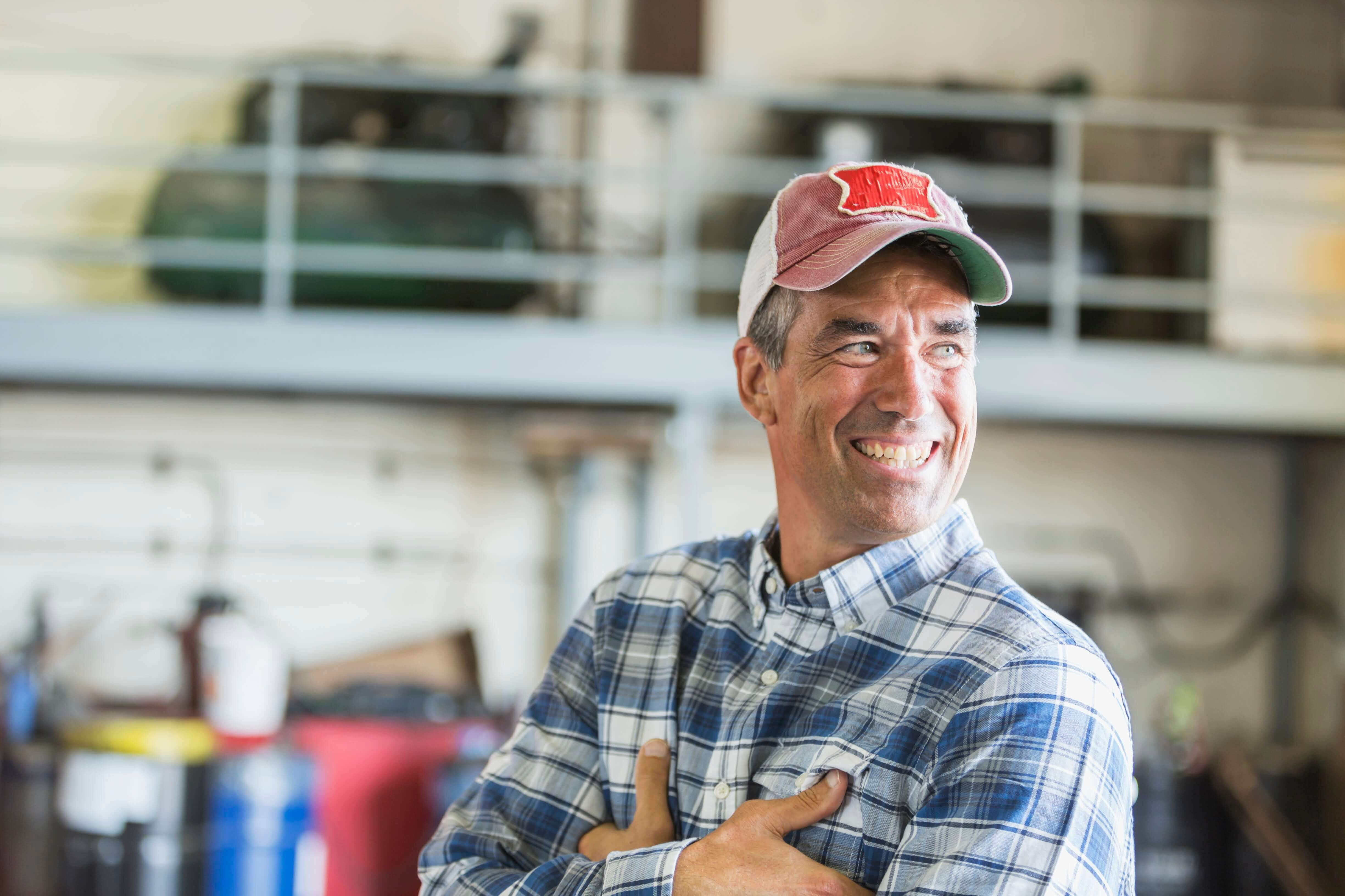 Smiling farmer in a ball cap and flannel