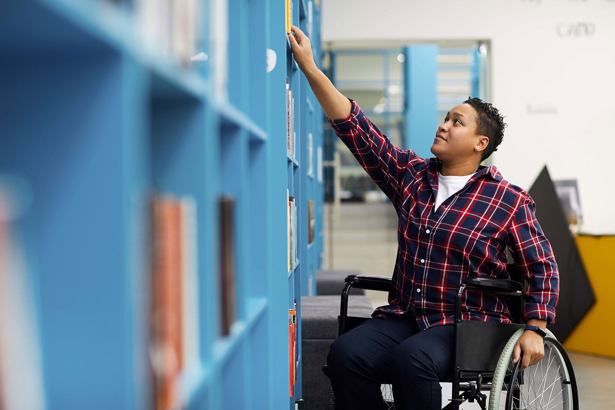 Student in wheelchair reaching for library book