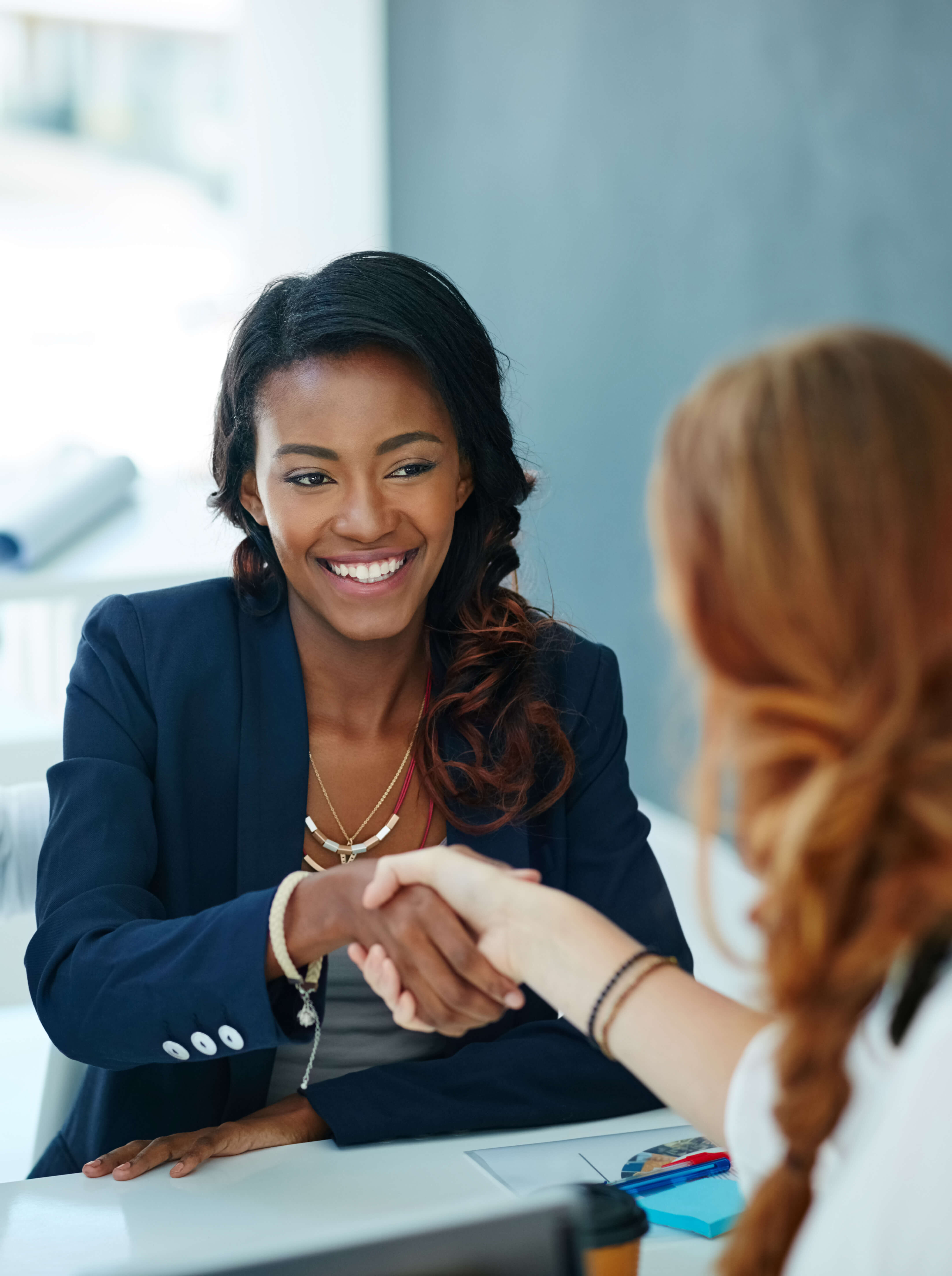 Two women in a business meeting shaking hands