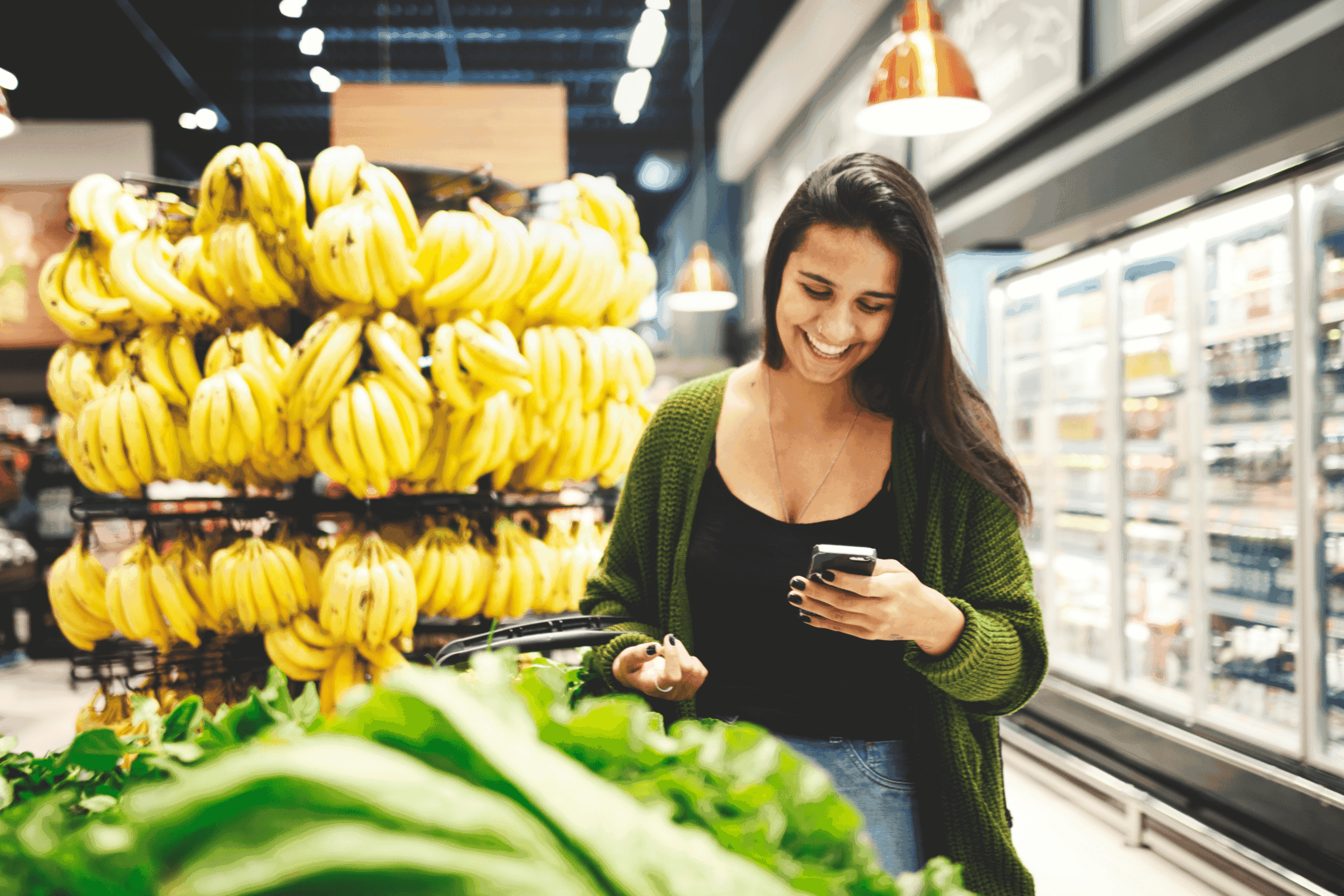 Woman grocery shopping and looking at phone