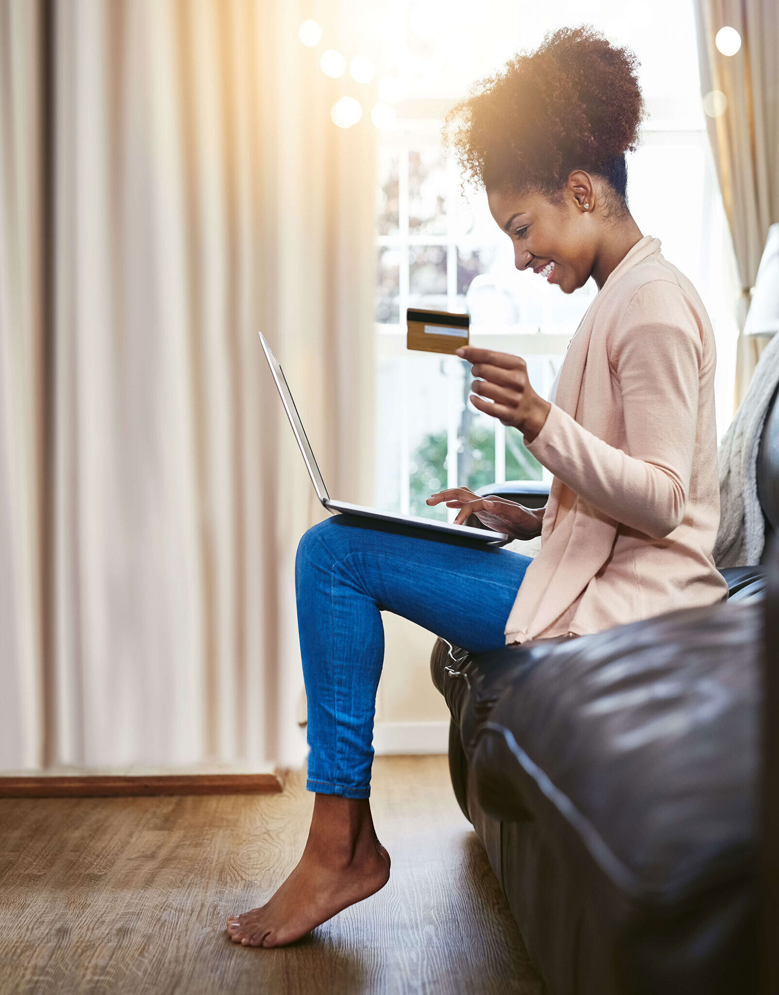 Woman smiling and sitting on couch with credit card