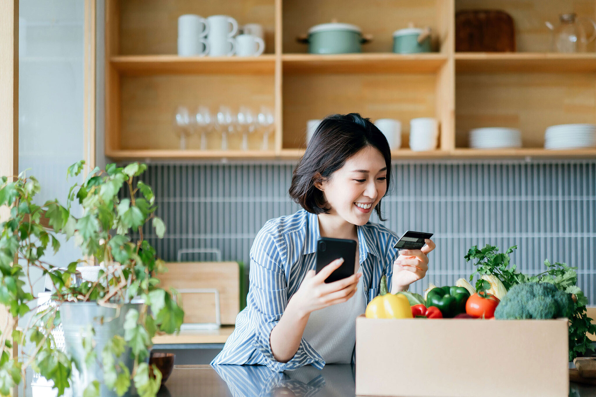 Woman smiling in kitchen with credit card and phone