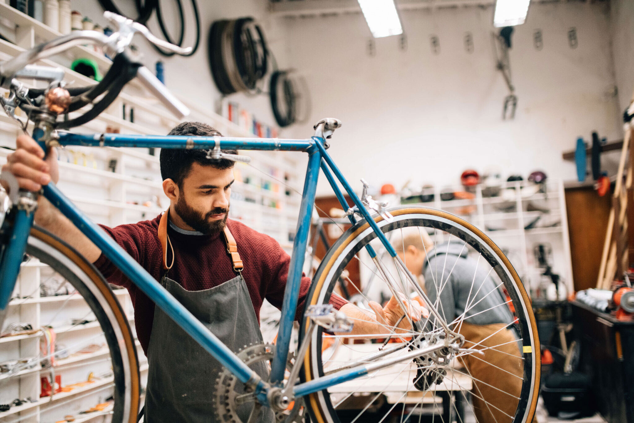 Young man fixing a bike in a bike shop