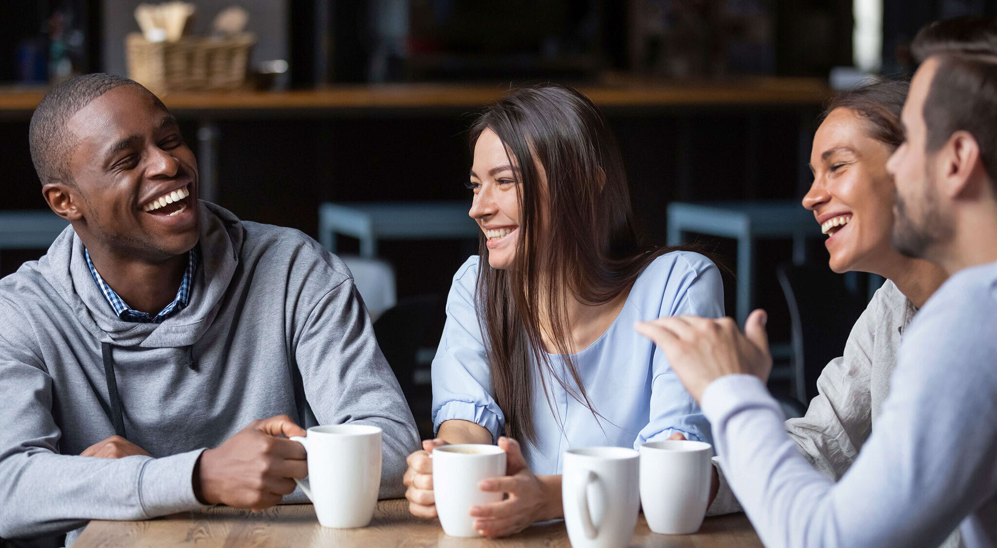 Young men and women laughing and talking over coffee