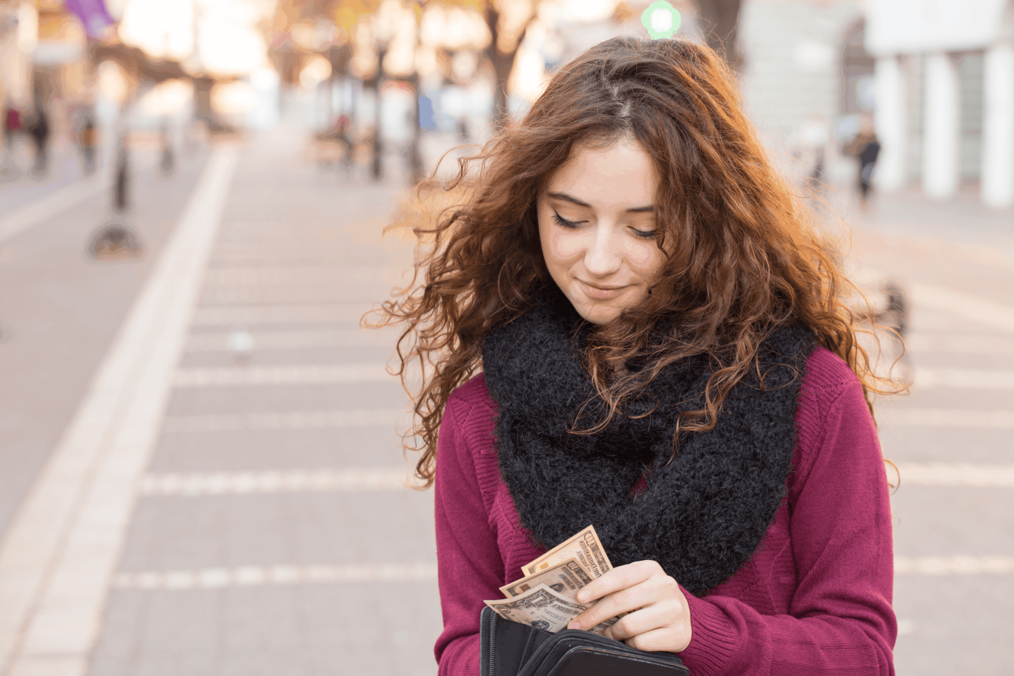 Young woman pulling dollar bills out of her wallet
