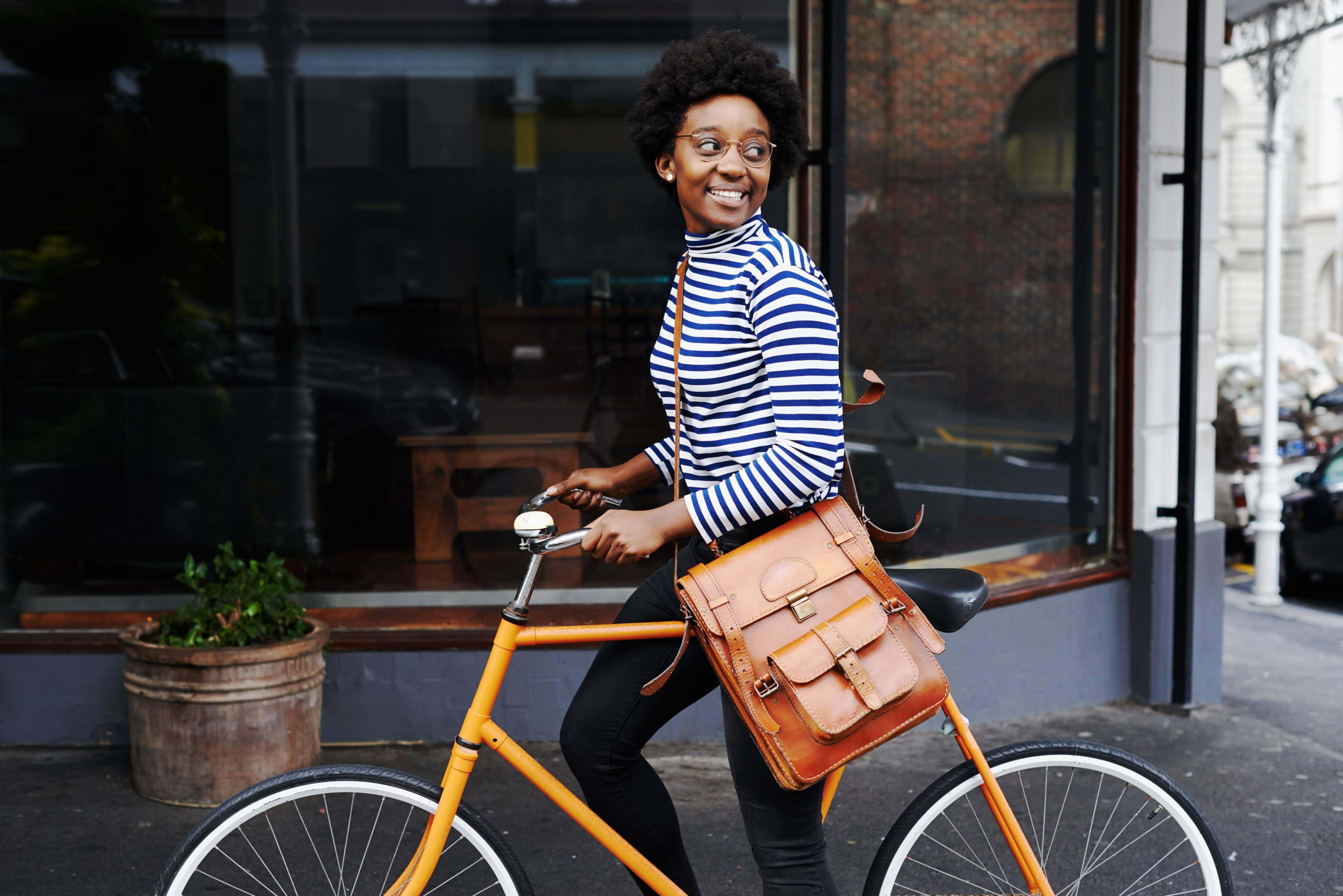 Young woman walking with her bike