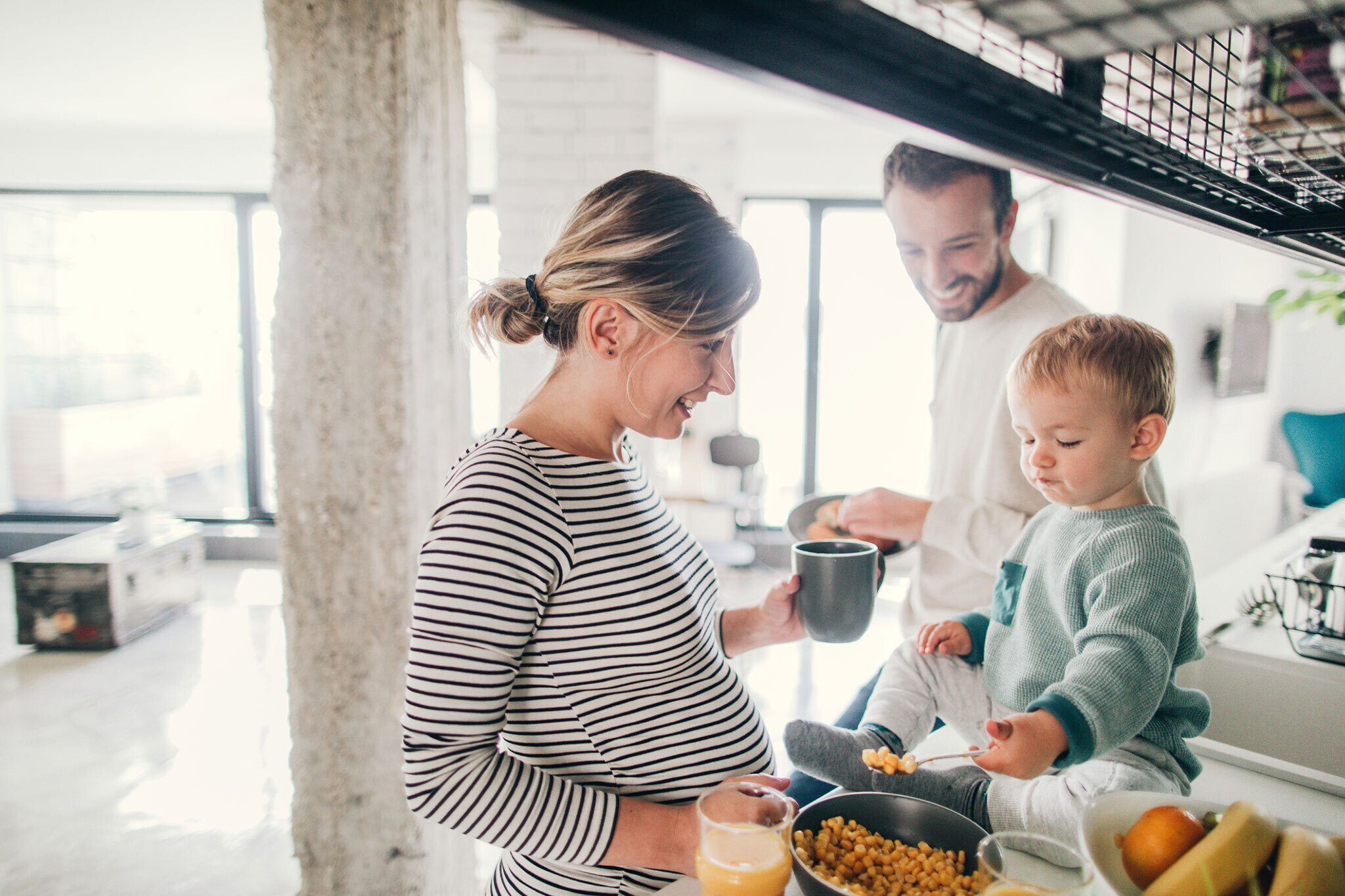 Millennial family eating breakfast and expecting baby